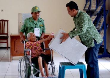 Petugas membantu warga lanjut usia memasukkan surat suara yang telah dicoblos di TPS 3 yang menempati Panti Jompo Wening Wardoyo, Kuncen, Ungaran Barat, Kabupaten Semarang, Jawa Tengah, Rabu (9/12).