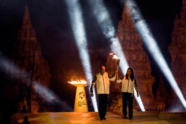 Legenda bulu tangkis Indonesia Susi Susanti (kanan) dan mantan atlet tenis nasional Yustedjo Tarik (kiri) membawa api obor dari India dan Mrapen yang telah dipersatukan saat Asian Games 2018 Torch Relay Concert di Kompleks Candi Prambanan, Sleman, DI Yogy