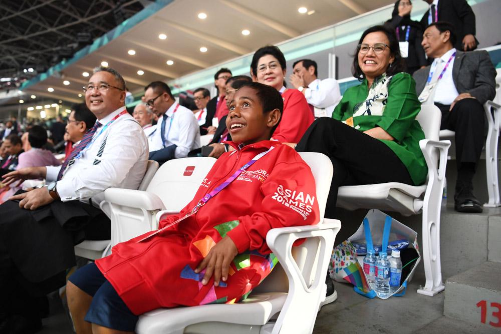 Yohanis Gama Marshall Lau alias Joni (tengah), siswa SMPN Silawan, Belu, Nusa Tenggara Timur duduk di antara menteri Kabinet Kerja saat menghadiri Upacara Pembukaan Asian Games ke-18 Tahun 2018 di Stadion Utama GBK, Senayan, Jakarta, Sabtu (18/8)