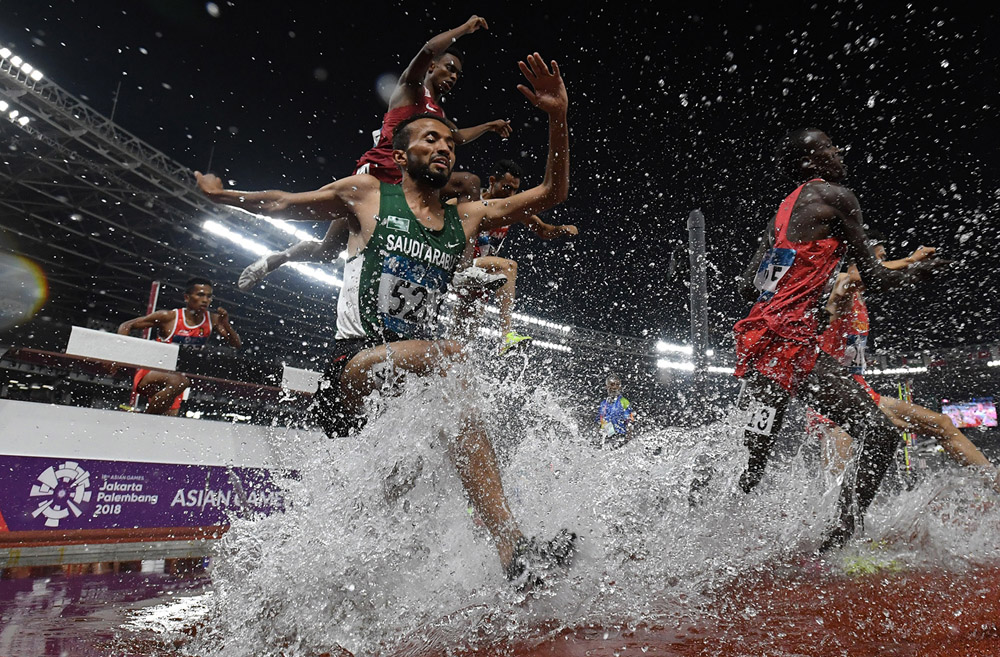 Sejumlah pelari melewati rintangan air saat final nomor Lari Halang Rintang 3.000M Putra Asian Games ke-18 Tahun 2018 di Stadion Utama Gelora Bung Karno Senayan, Jakarta, Senin (27/8).